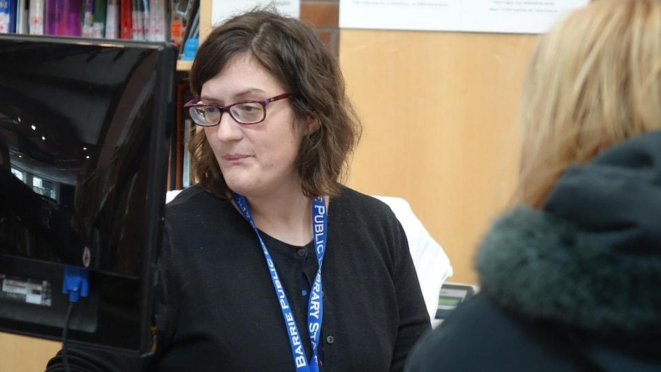 Une employée de la bibliothèque municipale de Barrie sert une cliente au comptoir.
