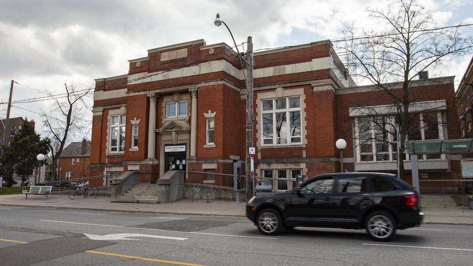 L'édifice devant lequel passe un véhicule.