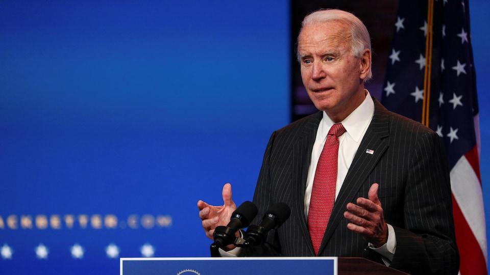 Joe Biden, s'adressant aux reporters, devant un drapeau américain
