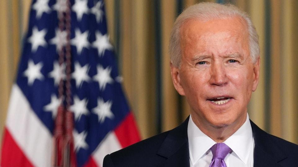 Joe Biden regarde la caméra devant un drapeau américain