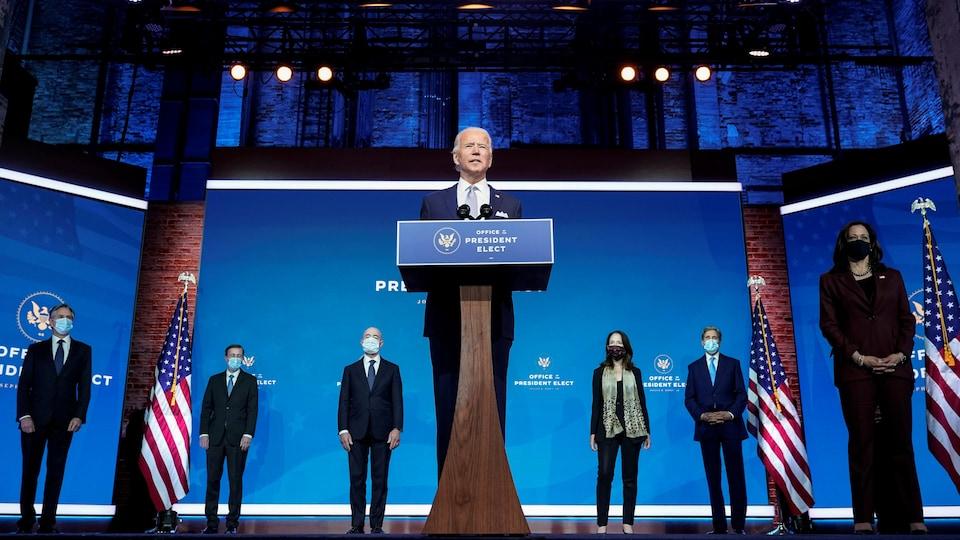 Joe Biden s'adresse aux journalistes en compagnie de ses nouveaux collaborateurs, Antony Blinken, Jake Sullivan, Alejandro Mayorkas, Avril Haines et John Kerry ainsi que la vice-présidente désignée, Kamala Harris, qui portent tous un masque.