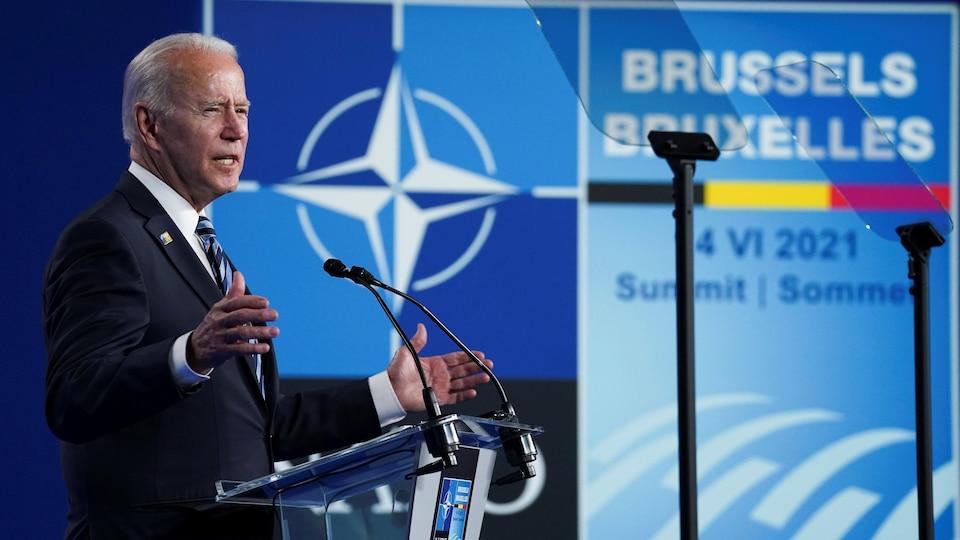 Devant un lutrin et des microphones, Joe Biden s'adresse aux journalistes, avec le logo du sommet de l'OTAN en arrière-plan.