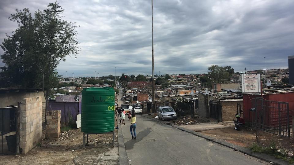 Des maisons petites et rudimentaires pressées les unes contre les autres, des déchets sur le sol.