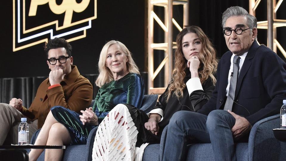 Les quatre personnes sont assises sur scène et répondent à des questions.