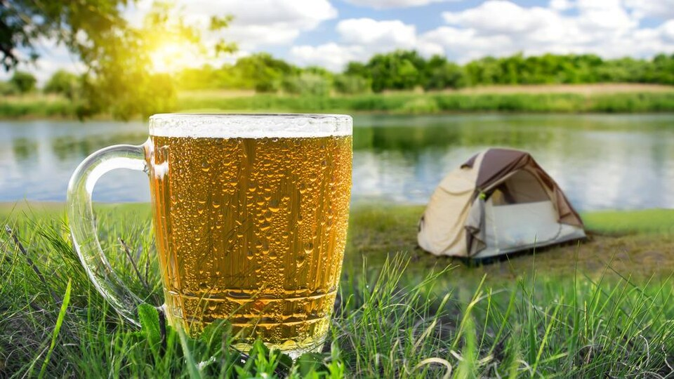 Un verre de bière froide en pleine nature avec, en arrière-plan, une tente, un lac ainsi qu'un soleil brillant