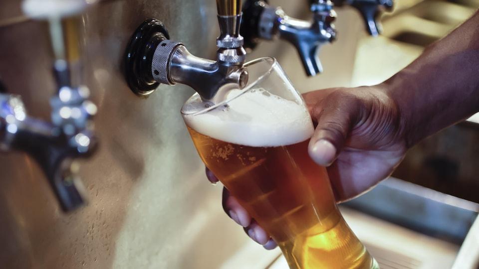 Un homme remplit un verre de bière en fût.