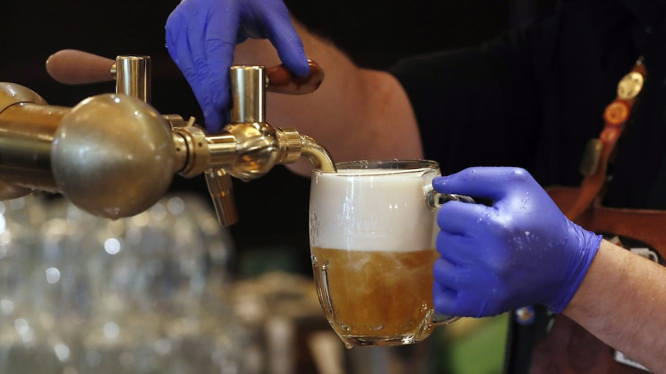 Un serveur ganté verse de la bière en fut dans une pinte.