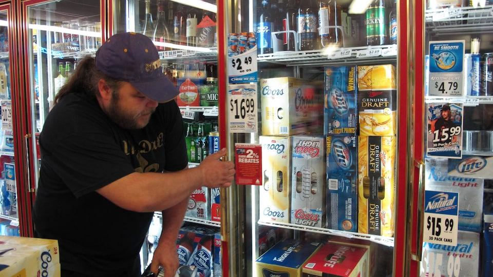 Un homme prend une caisse de bière dans le réfrigérateur d'un dépanneur.