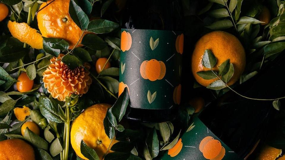 Des bouteilles de la bière Fortunello, de Four Winds, sont posées au milieu feuilles de plantes, de fleurs et de fruits.