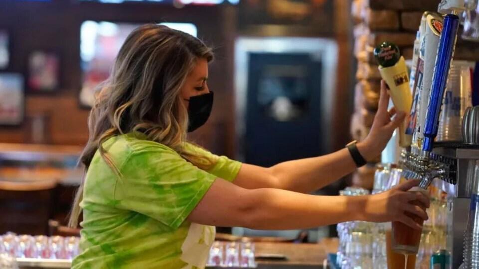 Une serveuse sert une bière dans un bar.