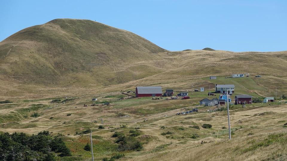 Une butte avec des maisons et une ferme à l'avant-plan.
