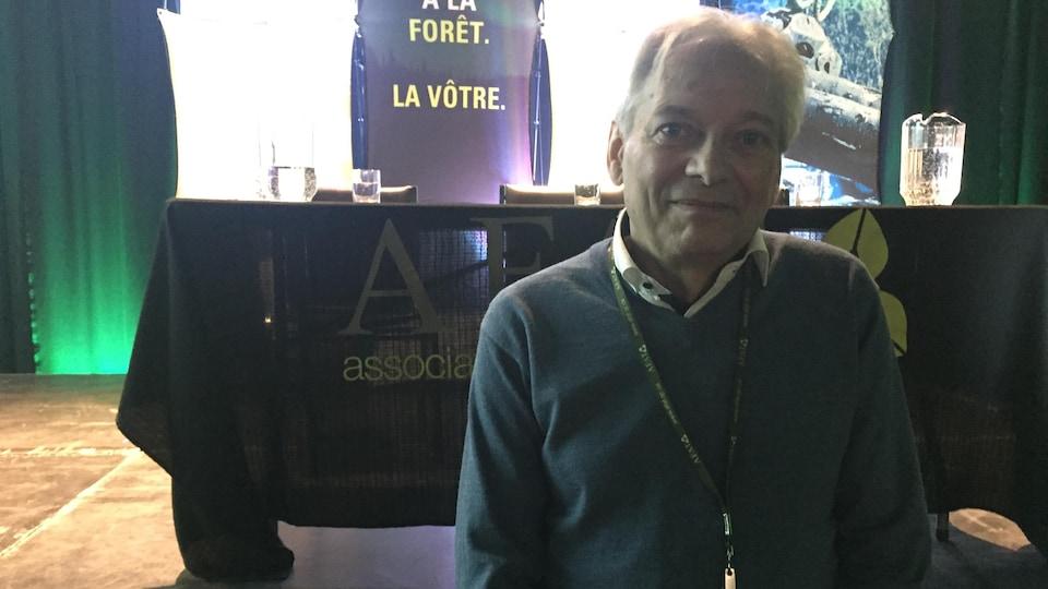 Luc Bouthillier pose devant la scène de la conférence.