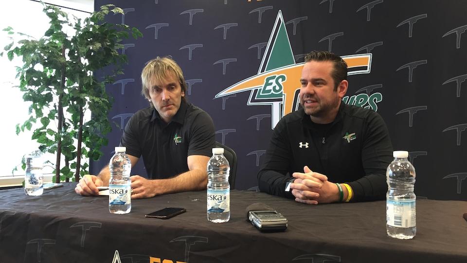 Deux hommes sont assis derrière une table à l'image des Foreurs de Val-d'Or lors d'une conférence de presse.