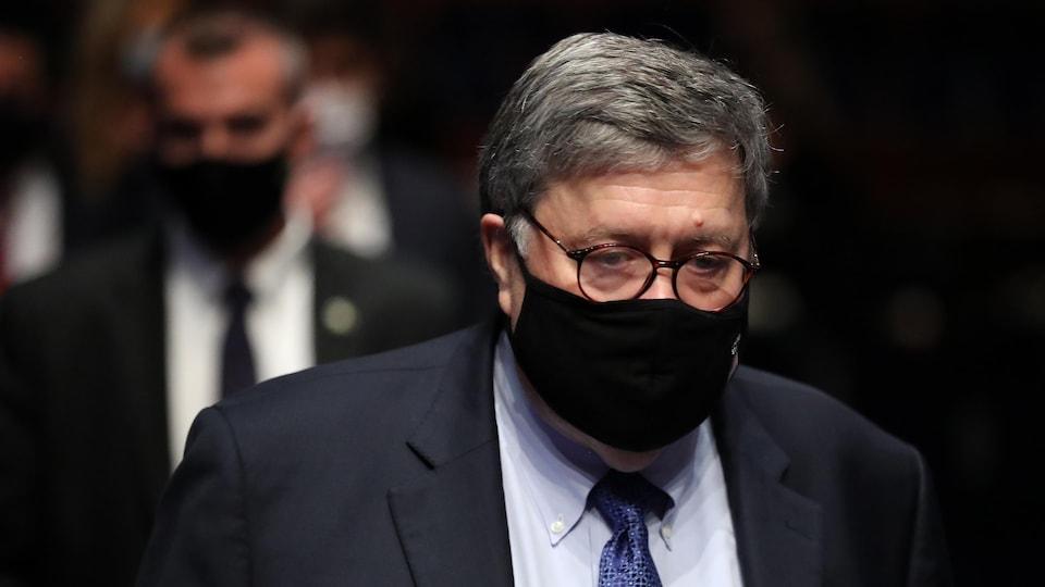 Bill Barr marche avec un masque.