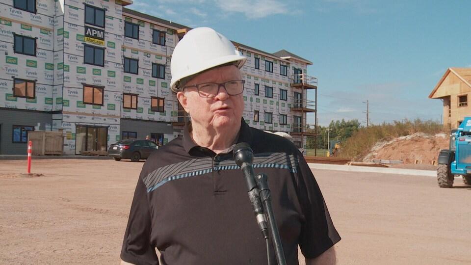 Bill Campbell devant un immeuble résidentiel en construction.