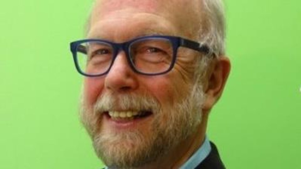 Un homme avec une barbe et des lunettes.