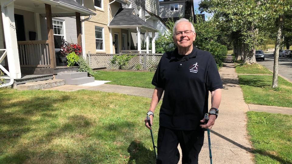 Un homme aîné avec des bâtons de marche, sur un trottoir.