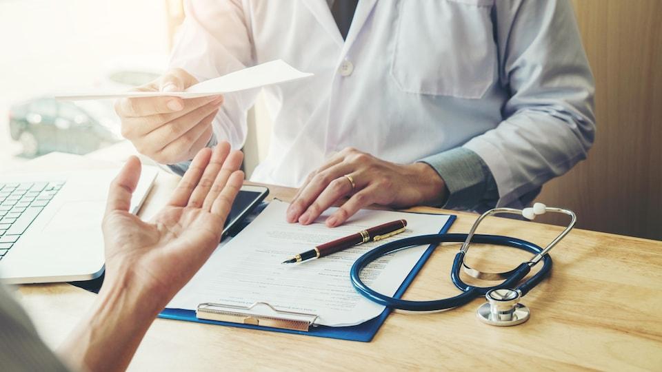 Un médecin remet un billet à une patiente.