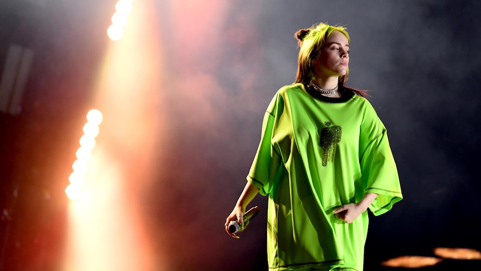 Billie Eilish porte un habit vert fluo lors d'un concert.