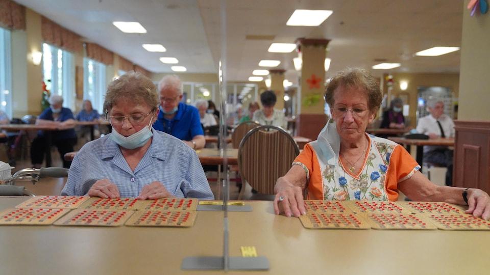 Des gens jouent au bingo dans une résidence pour personnes âgées.