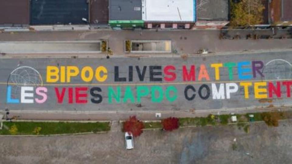 Sur le sol d'une route asphaltée, on peut lire en caractère majuscule multicolore : Bipoc lives matter, les vies napdc comptent.
