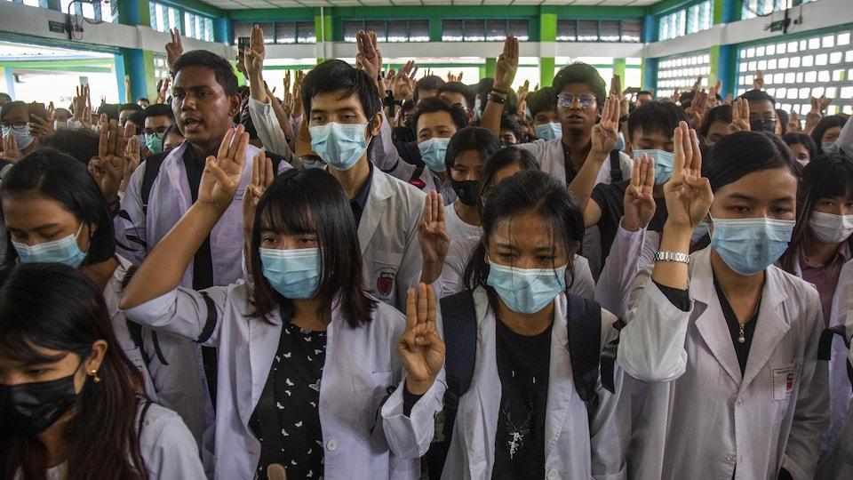 De jeunes personnes en blouse blanche, massées dans une salle et portant le couvre-visage, font un salut à trois doigts en signe de résistance.