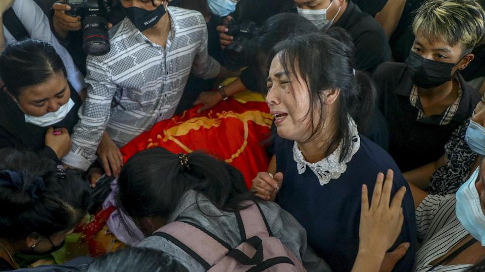 Une femme en pleurs entourée de nombreux jeunes qui transportent un cercueil.