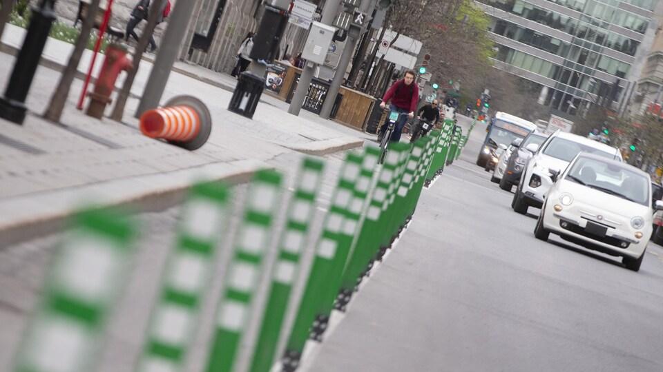Des cyclistes circulent sur une piste cyclable dans une rue de Montréal.