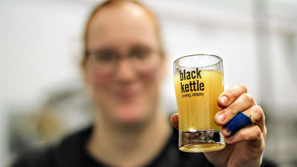 Une jeune femme tient un échantillon de bière dans une brasserie.