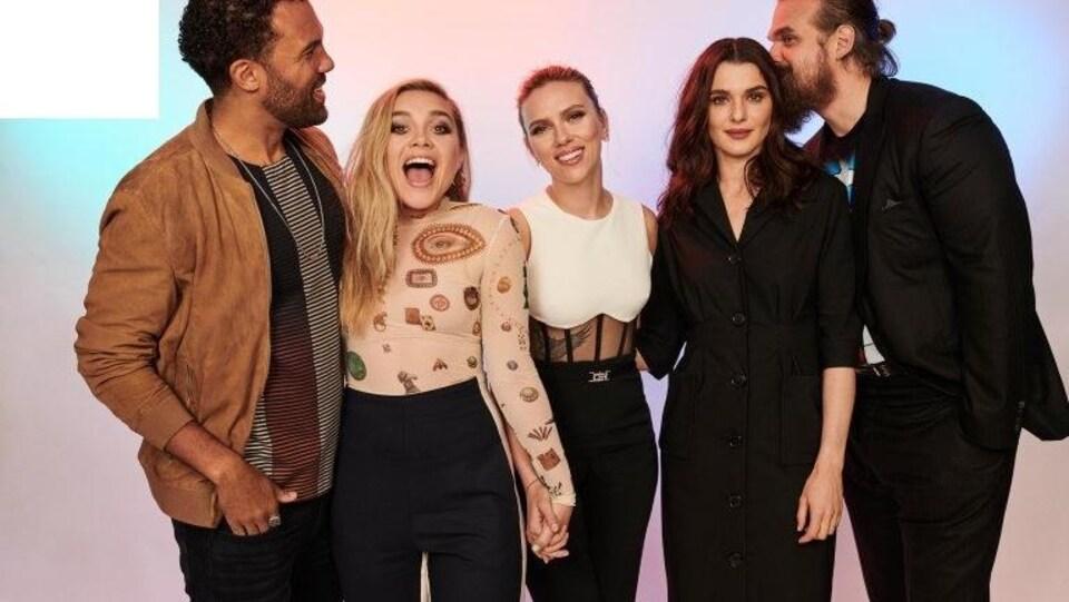 Les cinq personnes sourient et se tiennent l'un à côté de l'autre.