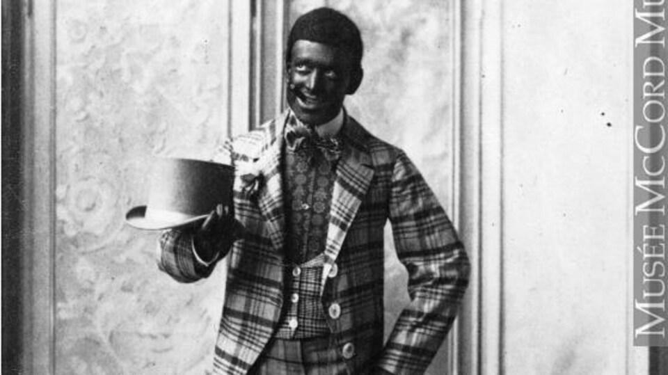 Un photo noir et blanc où l'artiste a le visage peinturé en noir.