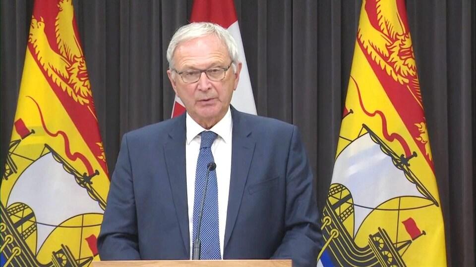 Blaine Higgs en conférence de presse devant des drapeaux du Nouveau-Brunswick.