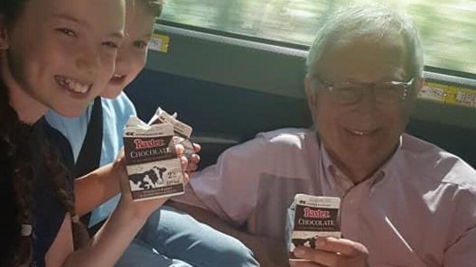 Blaine Higgs boit du lait au chocolat avec deux enfants.