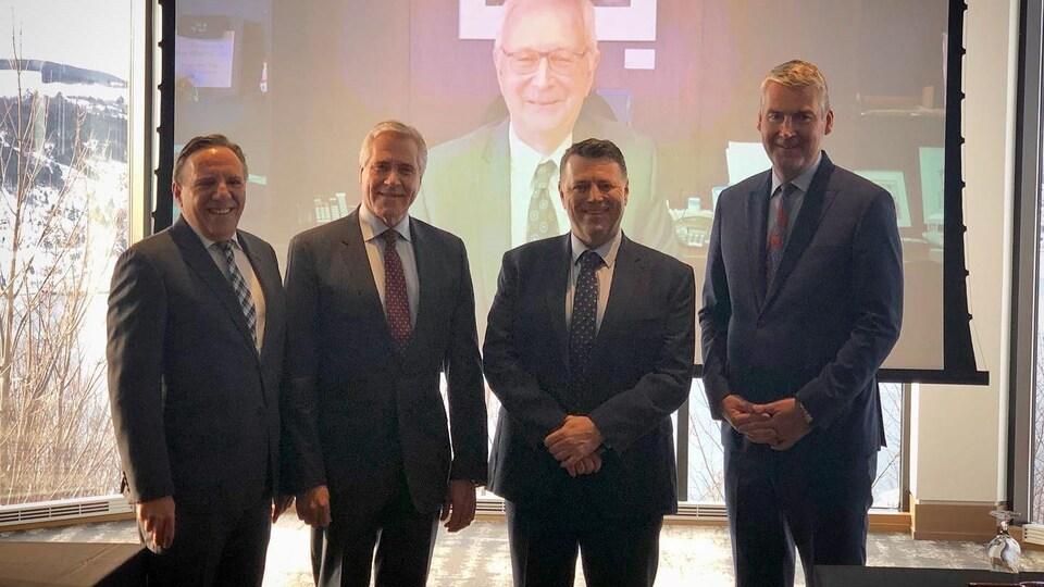 Les quatre premiers ministres de l'Atlantique devant un écran diffusant Blaine Higgs en vidéoconférence.