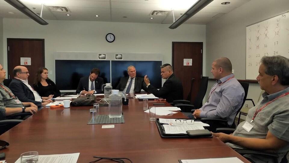 Le ministre de la Réduction du crime organisé, Bill Blair (quatrième à partir de la droite), et Isadore Day, PDG de Bimaadzwin, discutent lors d'une réunion tenue à Ottawa le 16 juillet dernier.