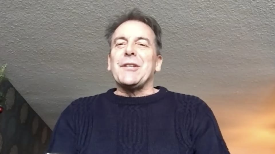 Un homme en entrevue via vidéoconférence.