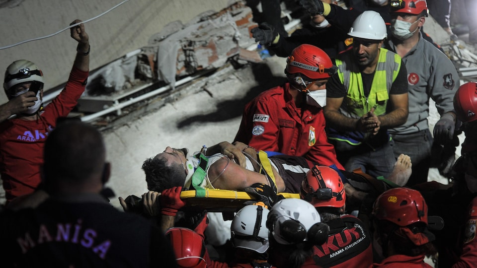 Des secouristes tiennent une civière.