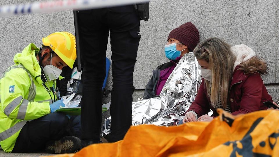 Deux femmes sont assises par terre contre un mur.