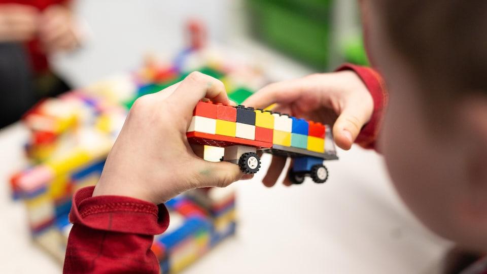 Un enfant qui tient des blocs de lego dans ses mains.