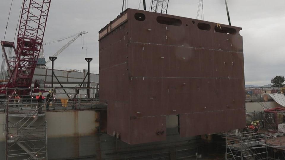 On voit un gros bloc brun, de côté, qui est hissé sur le chantier naval à l'aide de grues.