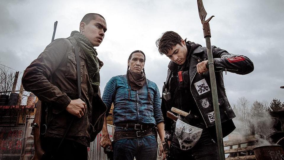 Trois hommes sont debout avec des armes aux mains.