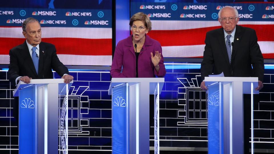 Une femme s'adresse aux militants démocrates lors d'un débat. Deux hommes l'écoutent.