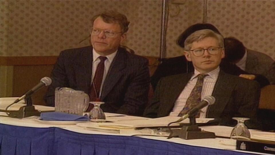 Deux hommes assis devant des microphones, à une table de négociation.
