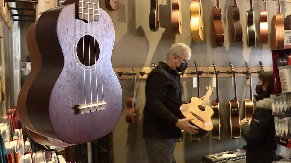 Un homme tient une guitare et la présente à une autre personne, dans un commerce.