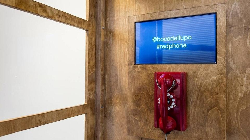L'intérieur d'une cabine téléphonique, avec un téléphone rouge et un écran.