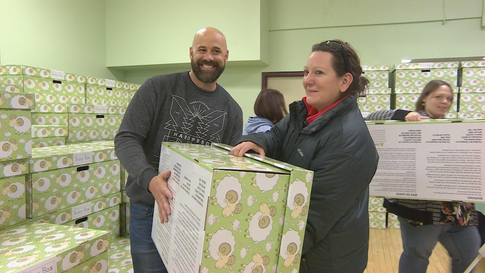 Un homme et une femme transportent une boîte verte, dans une pièce elle-même remplie de boîtes semblables.