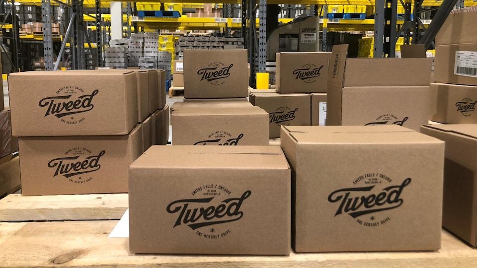 Des boîtes de cartons empilées, sur lesquelles on peut voir le logo de Tweed.