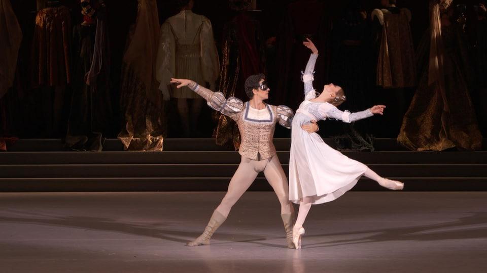 Un homme dansant le ballet tient dans son bras droit une ballerine effectuant une figure sur la pointe de son pied.