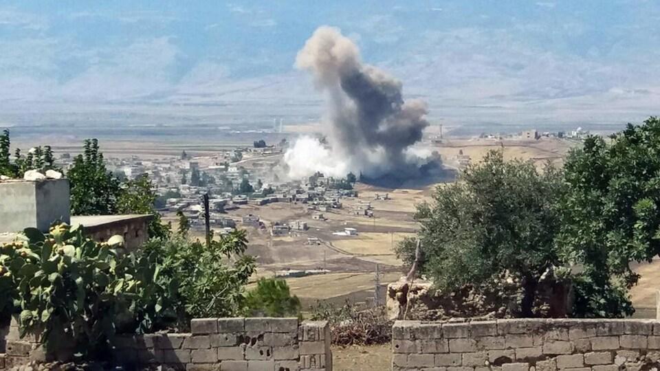 Une colonne de fumée s'élève à la suite d'une explosion dans un village syrien.