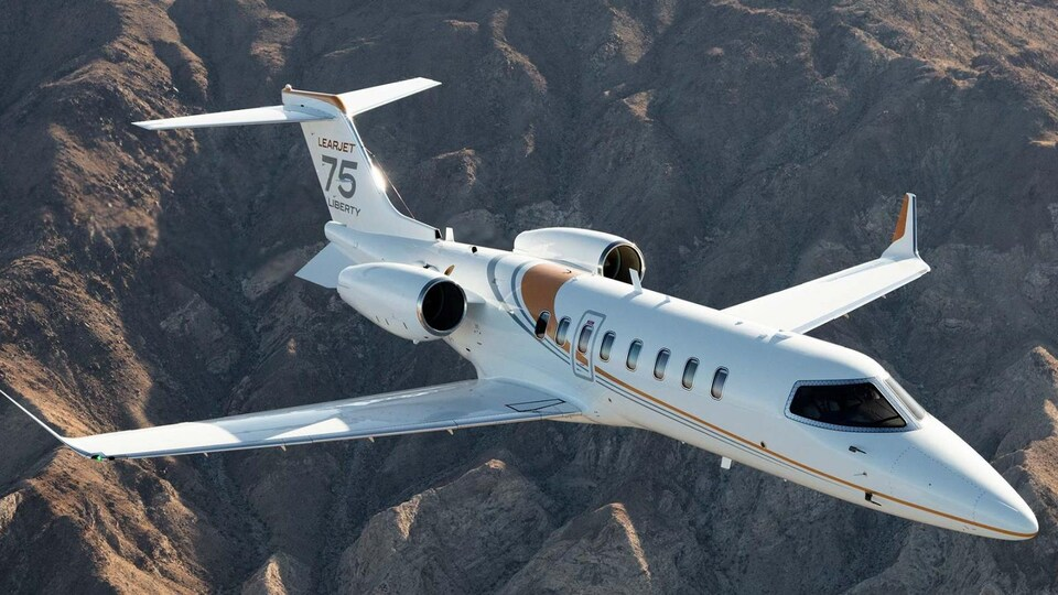 Un modèle de l'avion Learjet de Bombardier survole des montagnes.